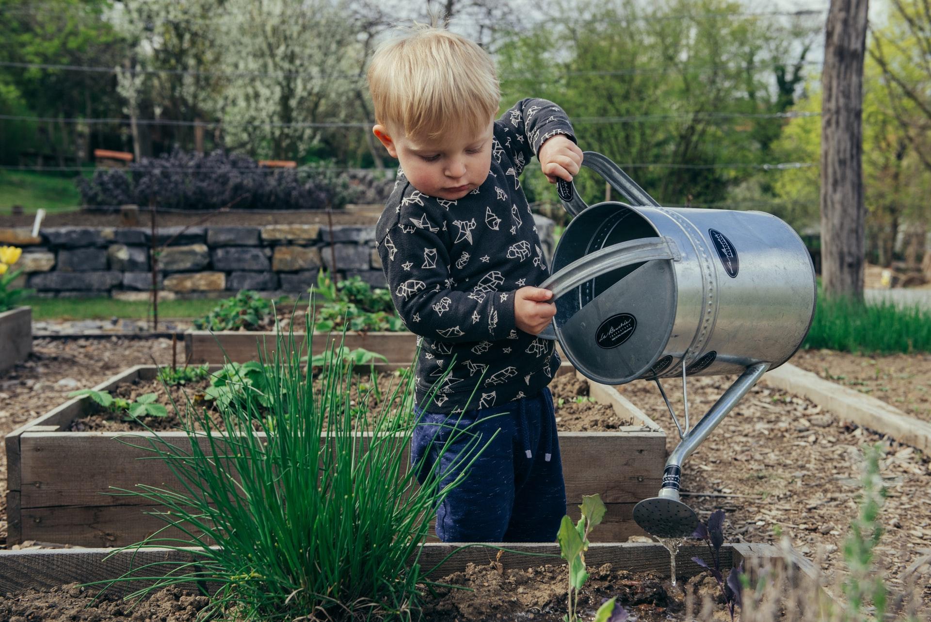 Kind gießt Blumen